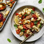 Sheet Pan Chicken Sausage and Veggies plated in a gray ceramic bowl over rice. The bowl has a gold fork in it and sits atop a creamy cement surface alongside a gray striped linen napkin, fresh basil leaves, & a small silver baking sheet with the baked chicken sausage & veggies.