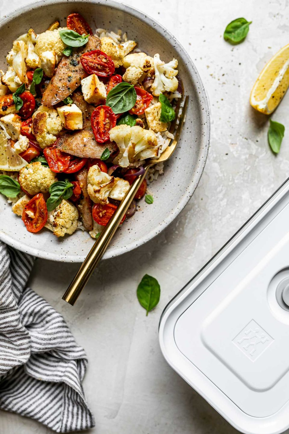 Sheet Pan Chicken Sausage and Veggies plated in a gray ceramic bowl over rice. The bowl has a gold fork in it and sits atop a creamy cement surface alongside a gray striped linen napkin, fresh basil leaves, & a Zwilling Fresh & Save container.