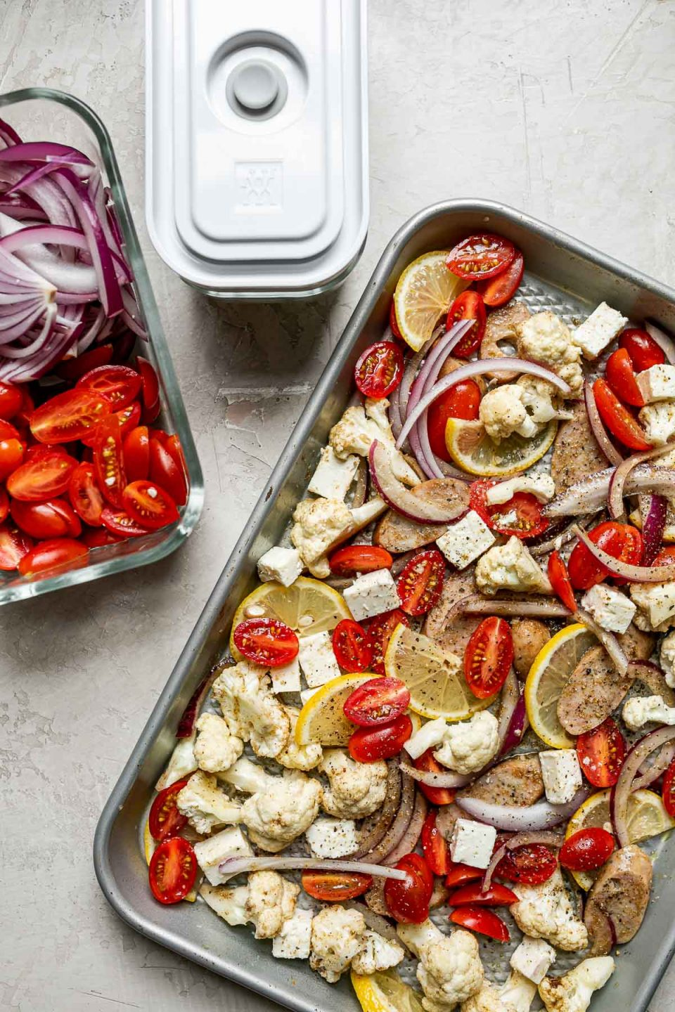 Sheet Pan Chicken Sausage and Veggies ingredients arranged on a silver quarter sheet pan atop a creamy cement surface alongside 2 Zwilling Fresh & Save containers with tomatoes & red onions.
