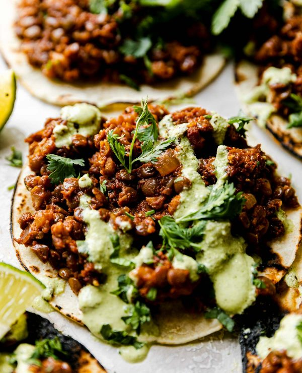 An angled close up shot of Cauliflower Lentil Tacos arranged on a white cement surface, topped with cilantro lime crema sauce & chopped cilantro. There are a few lime wedges surrounding the tacos.