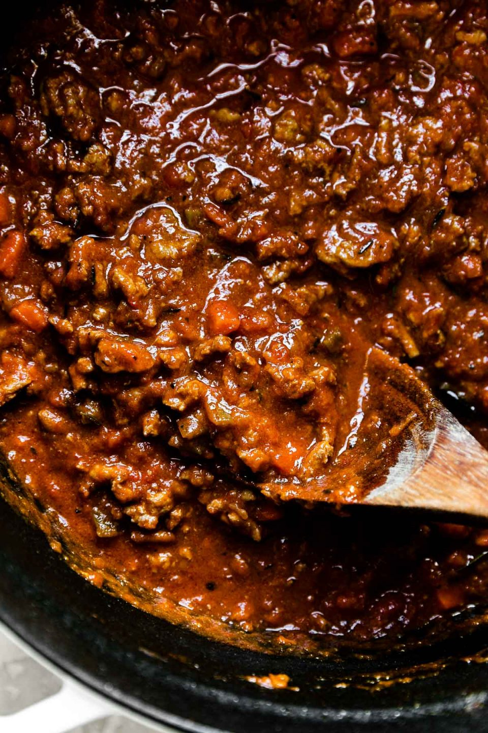 Weeknight bolognese sauce made with turkey in a large pot with a wooden spoon inside.