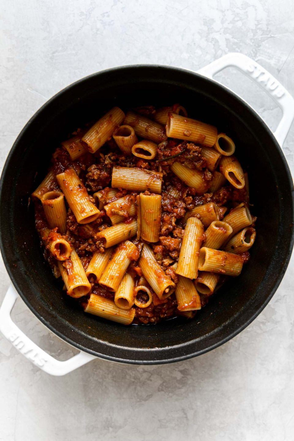 An overhead shot of a large pot filled with weeknight bolognese sauce mixed with rigatoni pasta noodles. The pot sits atop a creamy white surface.