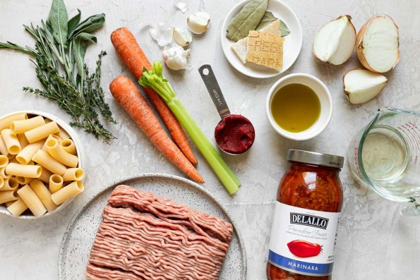 Weeknight Bolognese ingredients arranged on a creamy cement surface - olive oil, carrots, celery, yellow onion, 94% lean ground turkey, garlic, tomato paste, dry white wine, fresh rosemary, fresh sage, fresh thyme, bay leaves, parmesan rind, pasta sauce, chicken stock, & pasta noodles.