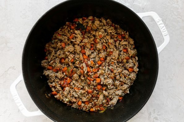 How to make weeknight bolognese, step 3: browning the turkey or meat of choice along with the soffritto in a large white pot. The pot sits atop a creamy white surface.