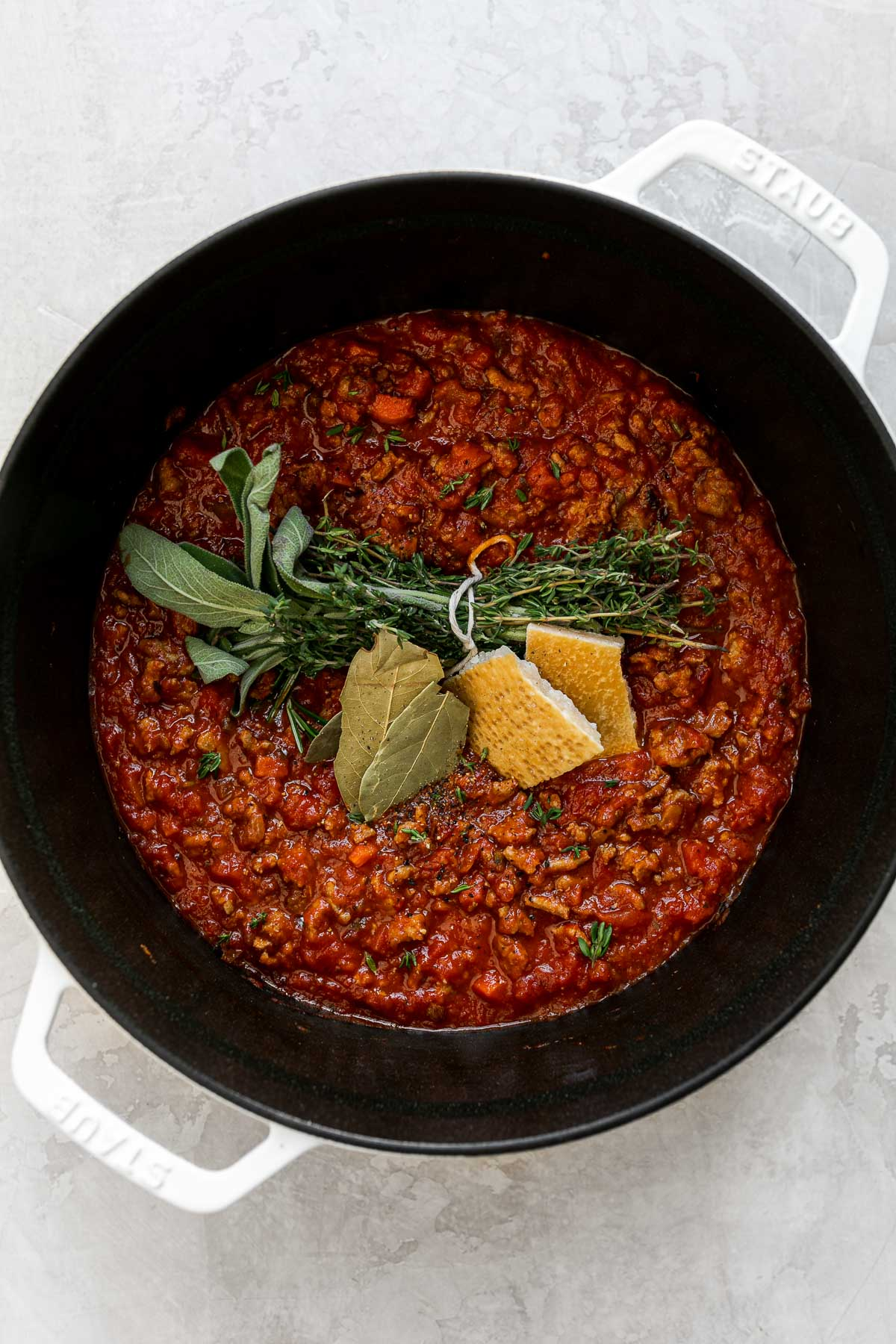 Weeknight bolognese sauce made with turkey in a large pot sits atop a creamy white surface. A tied bunch of fresh herbs, two dried basil leaves, & a parmesan rind have been added atop of the sauce to build flavor.