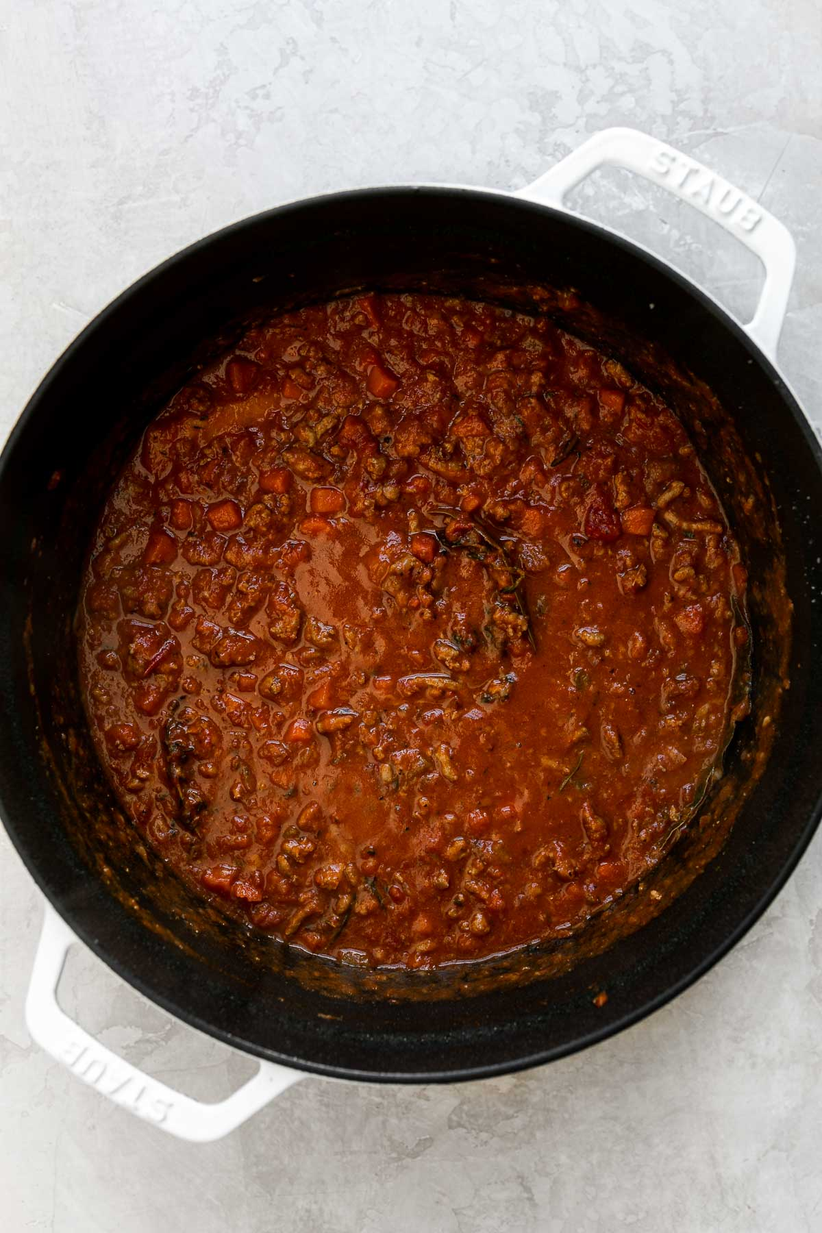 Weeknight bolognese sauce made with turkey in a large pot sits atop a creamy white surface.