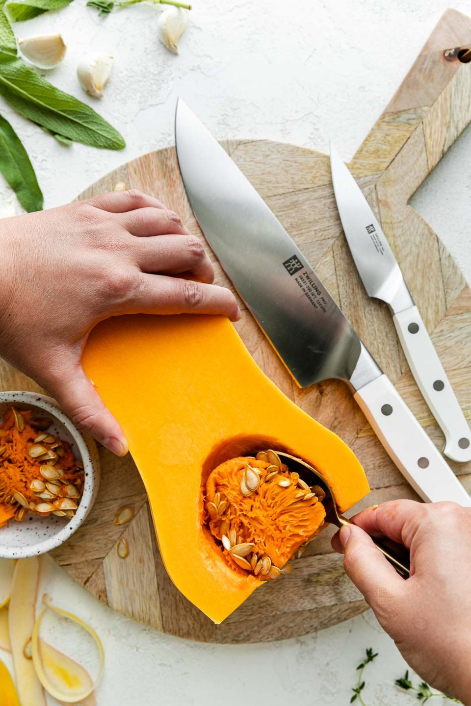 Half of a peeled butternut squash rests on top of a round wooden cutting board alongside a pair of Zwilling Pro Le Blanc Knives. A woman's hand holds the top portion of the butternut squash, while holding a spoon in the other hand using it to scoop out the butternut squash seeds. A small speckled ceramic bowl rests on the cutting board as well to collect the discarded butternut squash seeds. The cutting board sits atop a white textured surface while butternut squash peelings, fresh herbs, & cloves of garlic surround the cutting board.