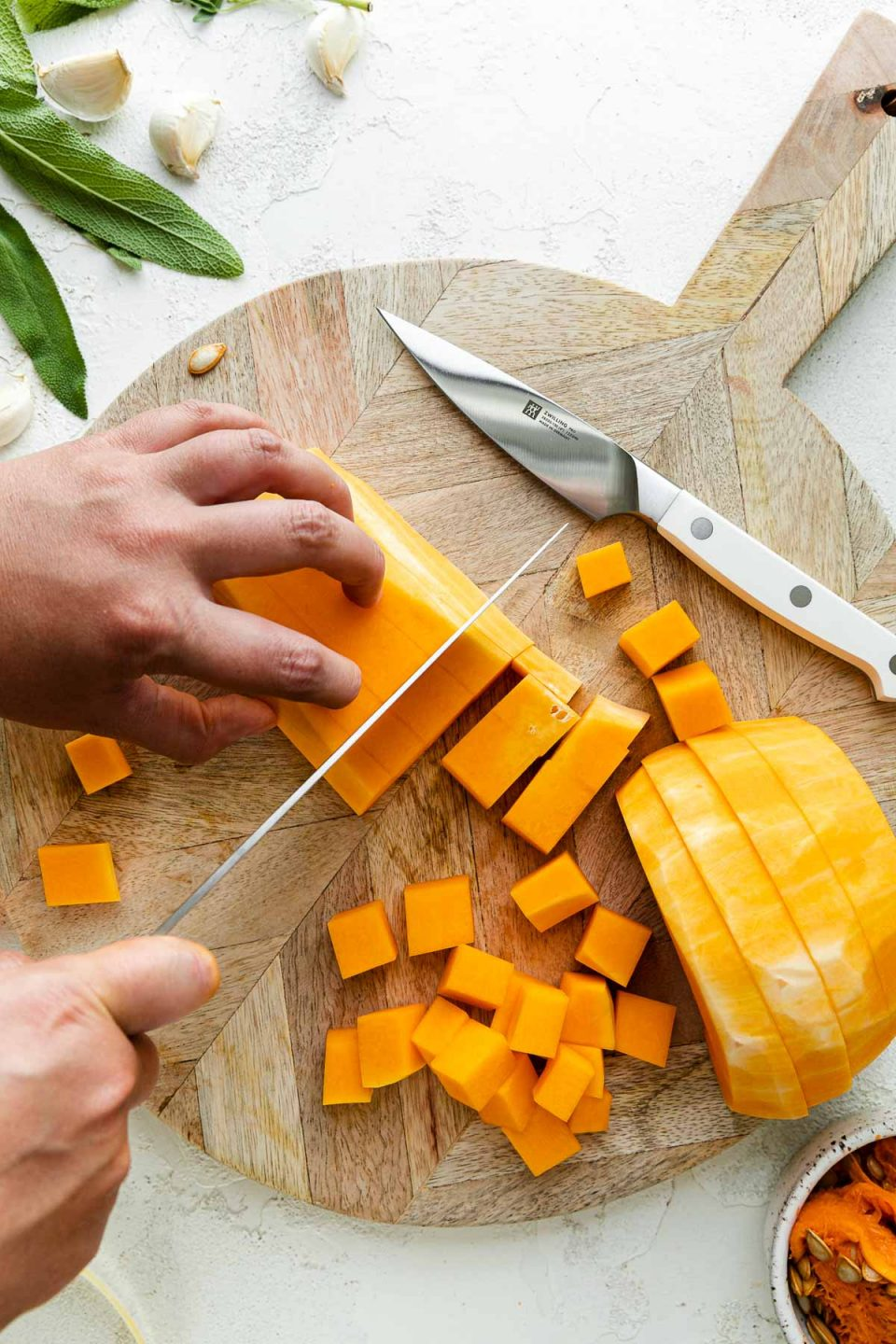 A peeled & cored butternut squash rests on top of a round wooden cutting board alongside a Zwilling Pro Le Blanc pairing knife. A woman's hands hold the top portion of a group of cut butternut squash, while using a knife to cut the squash into cubes with her other hand. Cubes of butternut squash rest on the cutting board & the cutting board sits atop a white textured surface while butternut squash peelings, fresh herbs, & cloves of garlic surround the cutting board.