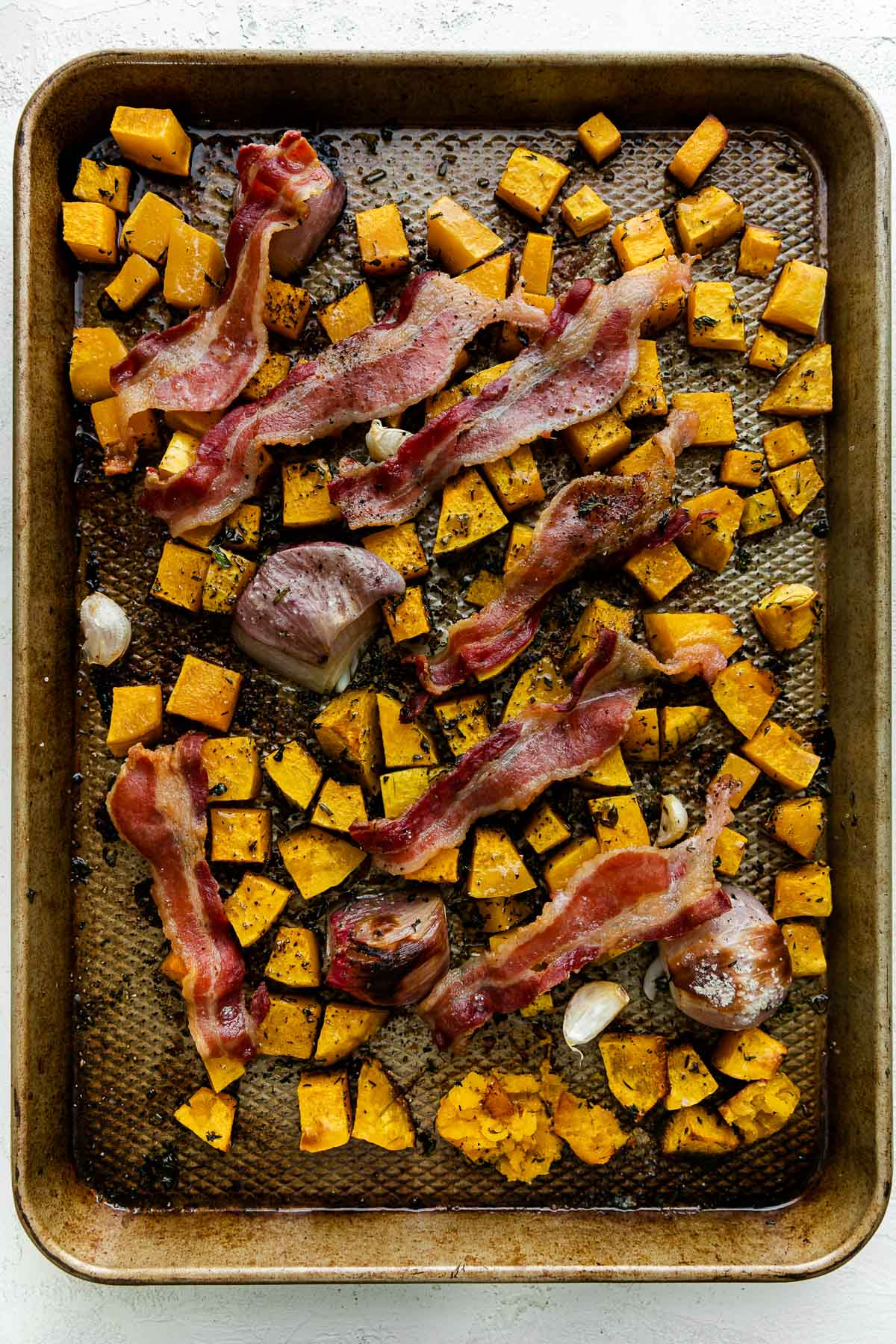 Cubed butternut squash, shallots, & garlic seasoned with olive oil & fresh herbs with bacon draped over top on a baking sheet after roasting. The baking sheet sits atop a white textured surface.