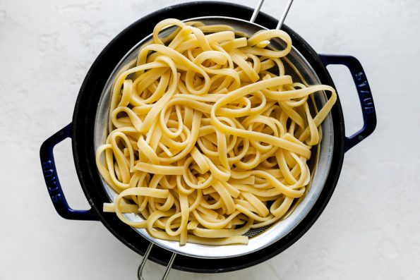 Al dente cooked linguine pasta noodles strained using a mesh strainer that rests inside of a Staub dutch oven. The Dutch oven rests atop a white textured surface.