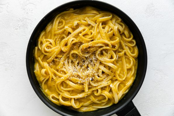 A small skillet filled with cooked linguine noodles tossed in creamy butternut squash pasta sauce. The noodles have been garnished with freshly grated parmesan & ground black pepper. The skillet sits atop a white textured surface.