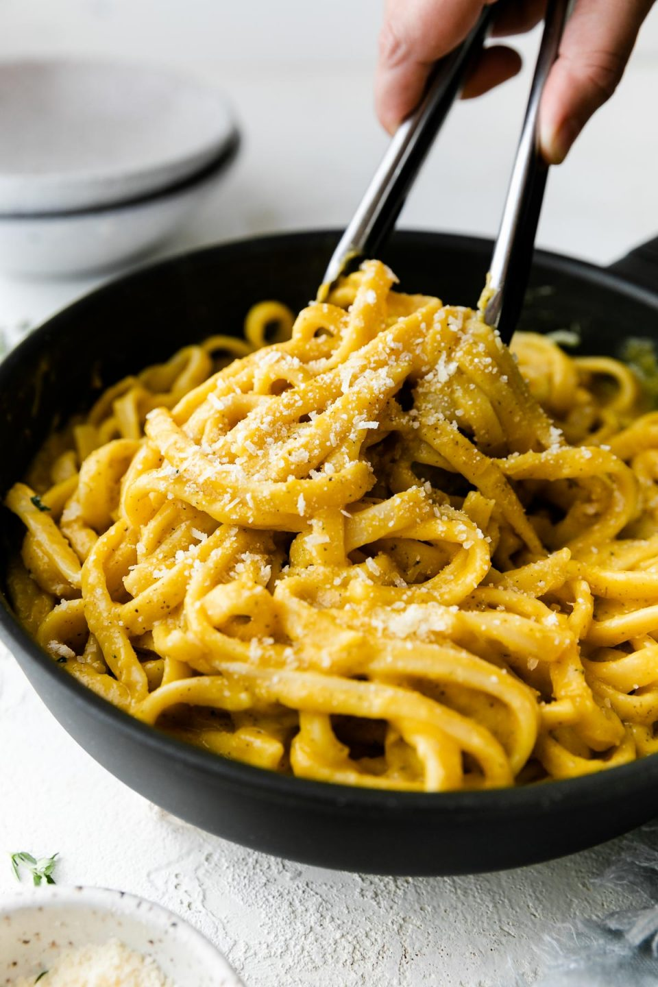 A small skillet filled with cooked linguine noodles tossed in creamy butternut squash pasta sauce. The noodles have been garnished with freshly grated parmesan & ground black pepper. A woman's hand picks up some of the pasta using a set of tongs. The skillet sits atop a white textured surface with an empty pasta bowl in the background & a small speckled bowl filled with grated parmesan cheese in the foreground.