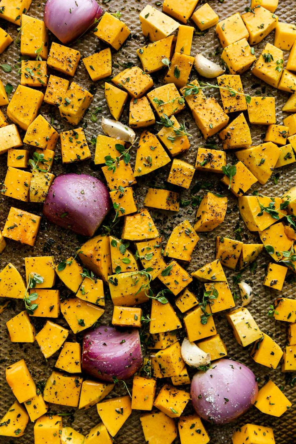Cubed butternut squash, shallots, & garlic seasoned with olive oil & fresh herbs on a baking sheet before roasting.