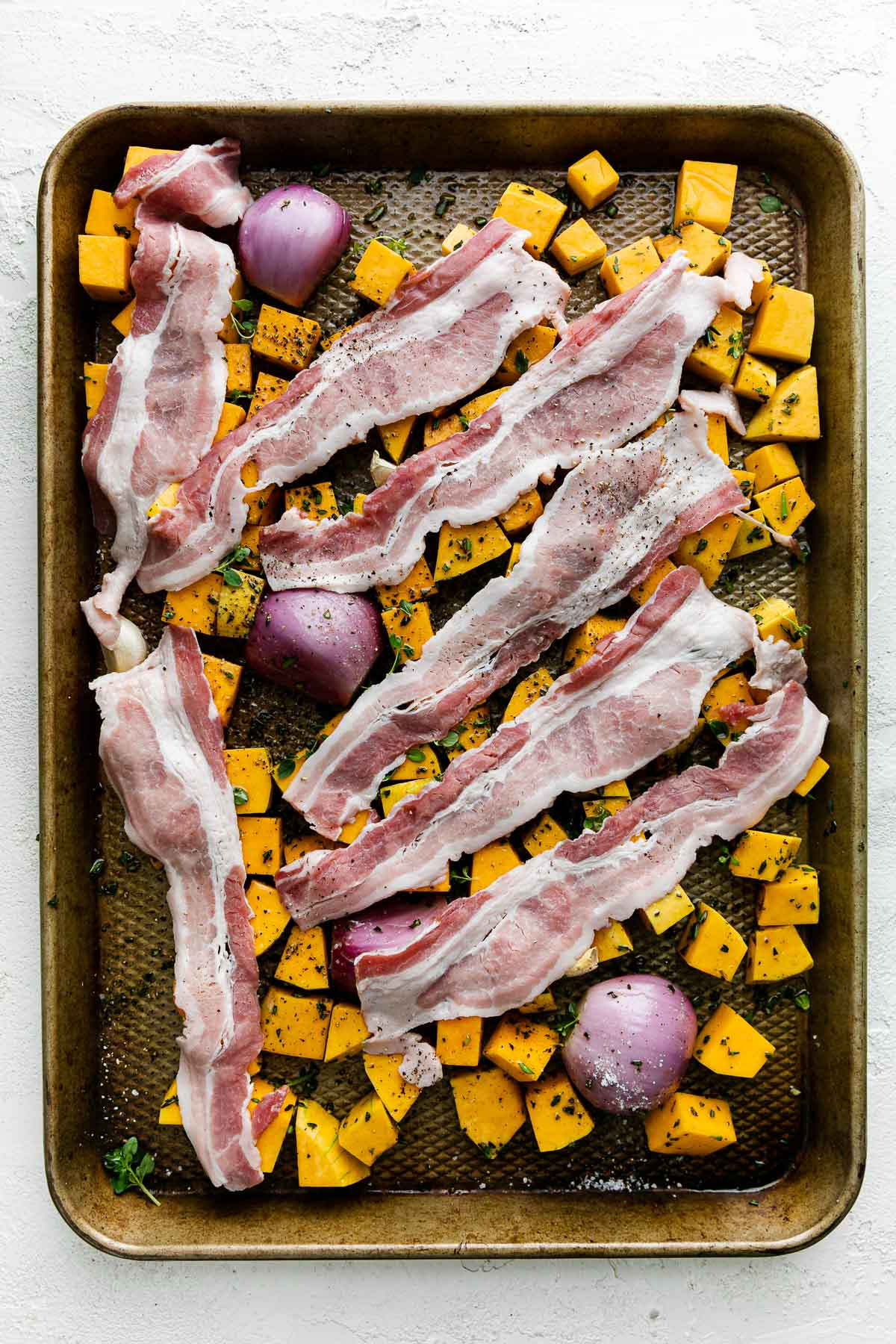 Cubed butternut squash, shallots, & garlic seasoned with olive oil & fresh herbs with bacon draped over top on a baking sheet before roasting. The baking sheet sits atop a white textured surface.