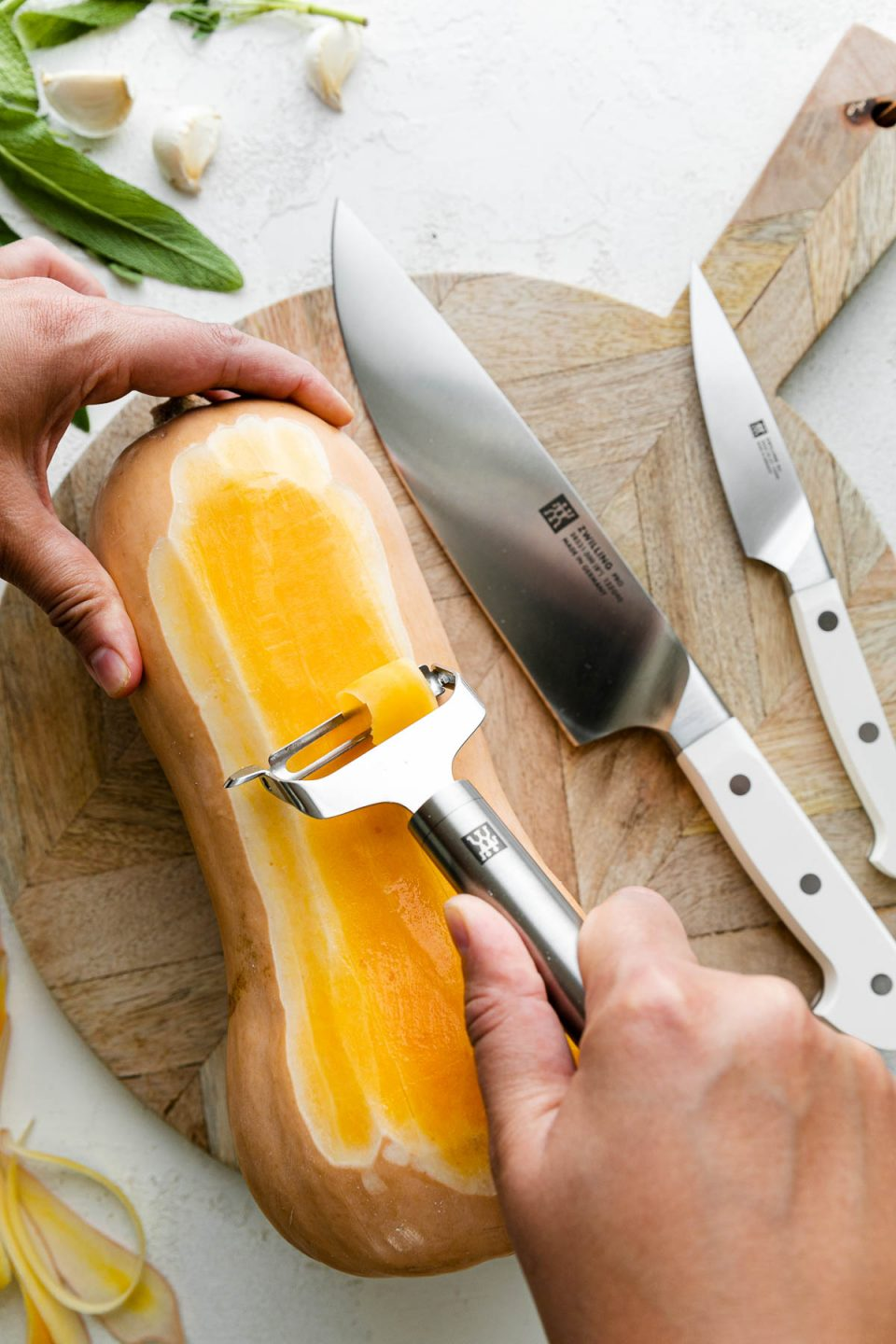 A whole butternut squash rests on top of a round wooden cutting board alongside a pair of Zwilling Pro Le Blanc Knives. A woman's hand holds the top portion of the butternut squash, while holding a Zwilling Pro Y-Peeler in the other hand to peel the squash. The cutting board sits atop a white textured surface while butternut squash peelings, fresh herbs, & cloves of garlic surround the cutting board.