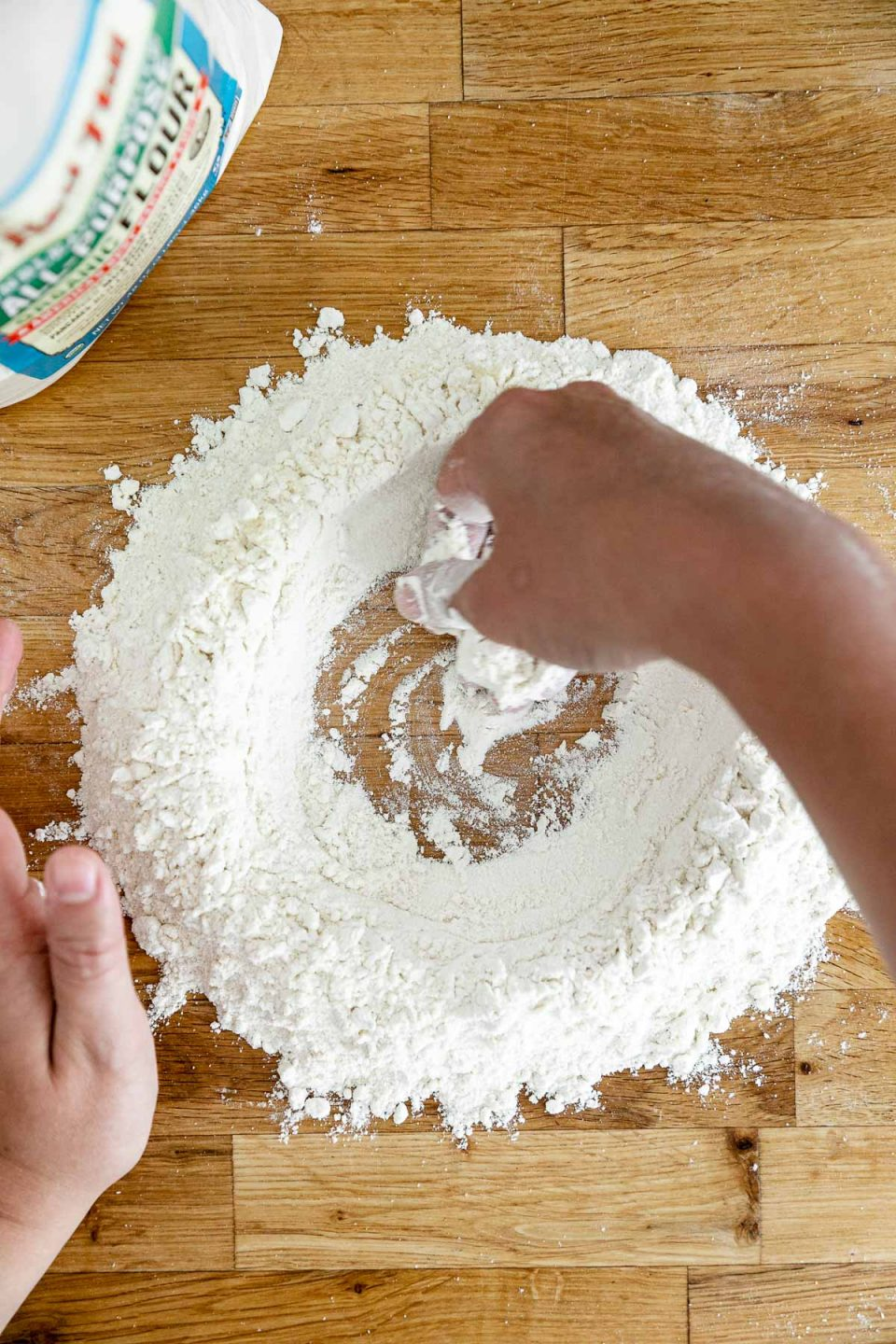 How to Make Homemade Pasta, Step 1: Mixing the flours. An overhead shot of Jess of Plays Well With Butter creating a large well in the center of a flour mixture with her hands. The well of flour sits atop a butcher block counter top and will be used to create fresh pasta dough.