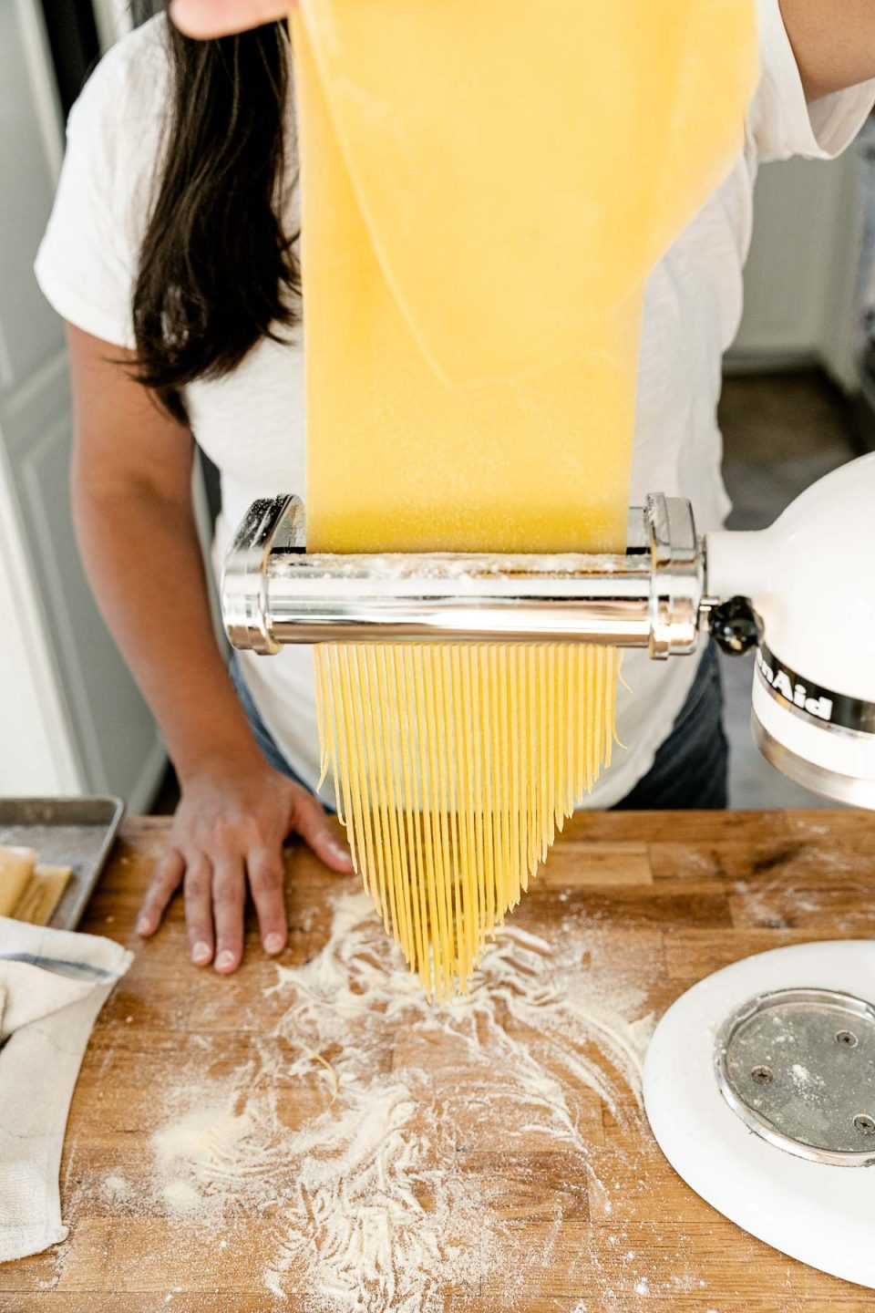 Jess of Plays Well With Butter feeds a large sheet of fresh pasta dough through a KitchenAid pasta cutting attachment connected to a Stand Mixer. As the pasta dough is fed through the cutter, the dough is cut into single strands of spaghetti. The Stand Mixer rests atop a butcher block countertop. The countertop has been lightly dusted with flour and an aluminum baking sheet also sits on top of the countertop and is covered by a kitchen towel.
