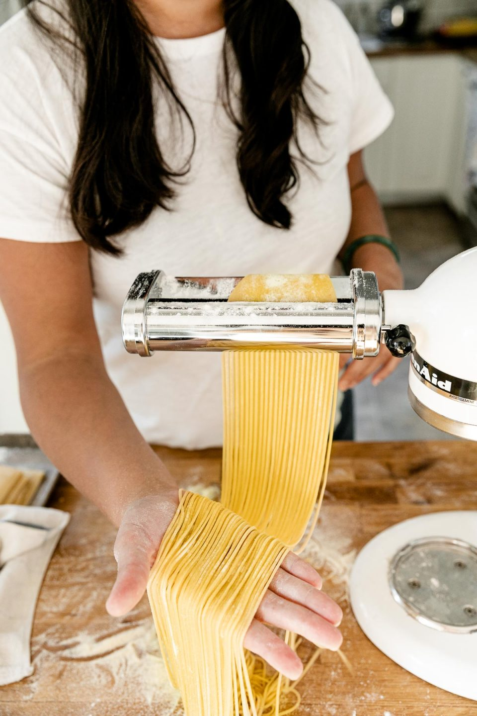 Jess of Plays Well With Butter feeds a large sheet of fresh pasta dough through a KitchenAid pasta cutting attachment connected to a Stand Mixer. As the pasta dough is fed through the cutter, the dough is cut into single strands of spaghetti. Her right hand catches the spaghetti noodles and lifts them up with a flat palm to display the cut noodles. The Stand Mixer rests atop a butcher block countertop. The countertop has been lightly dusted with flour and an aluminum baking sheet also sits on top of the countertop and is covered by a kitchen towel.