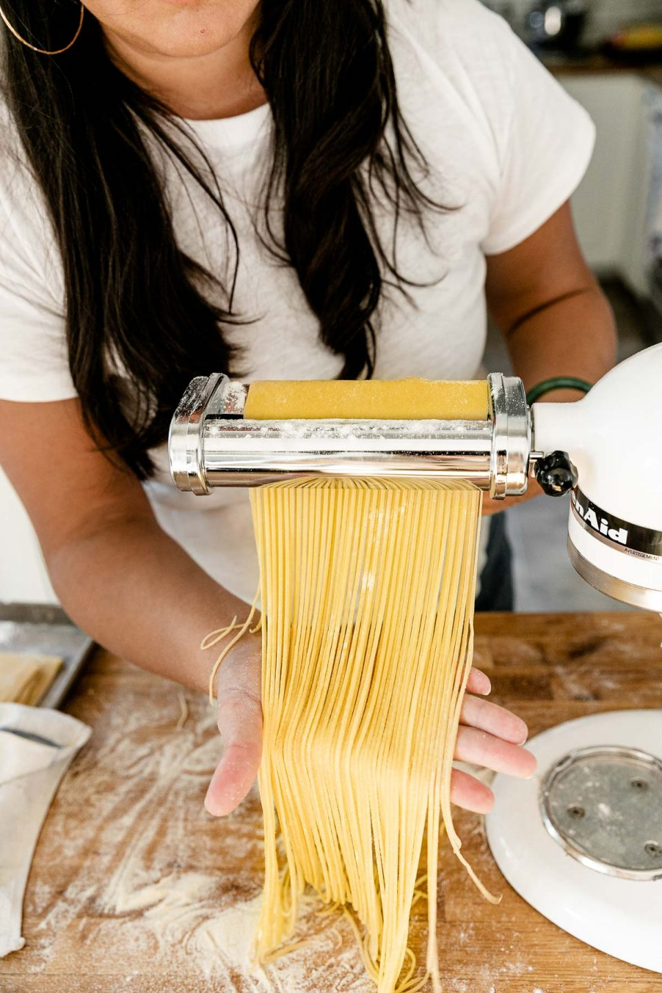 Jess of Plays Well With Butter feeds a large sheet of fresh pasta dough through a KitchenAid pasta cutting attachment connected to a Stand Mixer. As the pasta dough is fed through the cutter, the dough is cut into single strands of spaghetti. Her right hand catches the spaghetti noodles and lifts them up slightly with a flat palm to display the cut noodles and allow them to rest gently on the countertop. The Stand Mixer rests atop a butcher block countertop. The countertop has been lightly dusted with flour and an aluminum baking sheet also sits on top of the countertop and is covered by a kitchen towel.