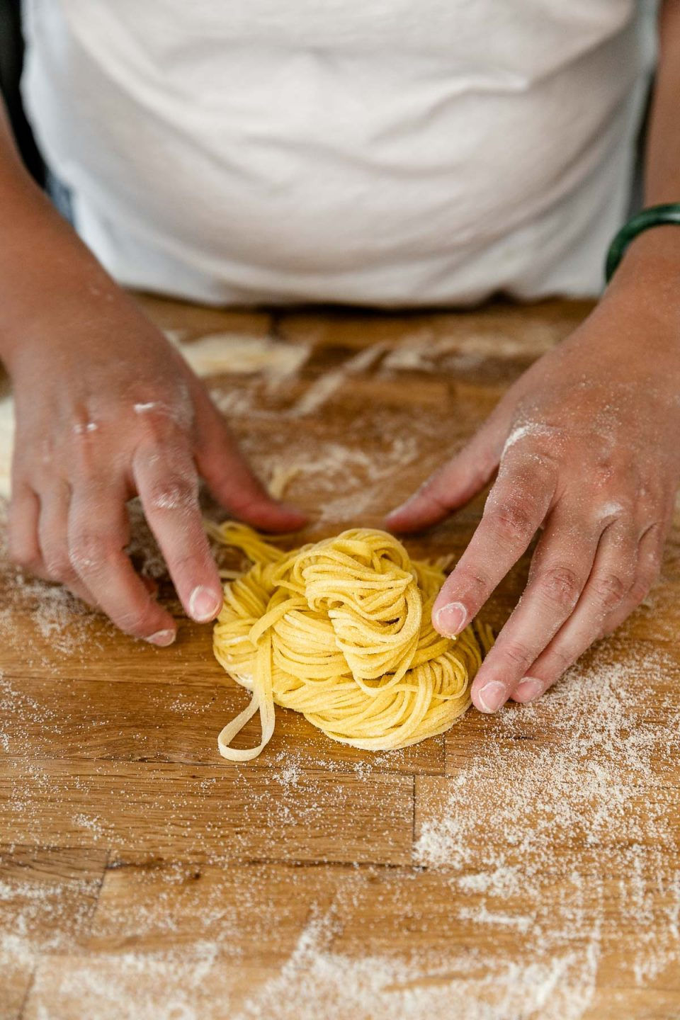 A side angle shot of a woman's hands forming a bundle of fresh pasta from homemade pasta dough cut into spaghetti noddles. The bundle rests atop a butcher block countertop that is dusted with semolina flour.