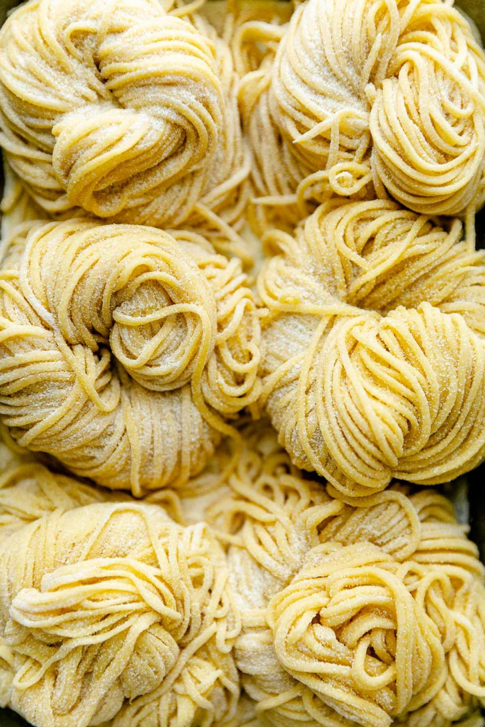 A close up of six bundles of fresh pasta cut into spaghetti noodles are arranged on a small aluminum baking sheet and dusted with semolina flour.
