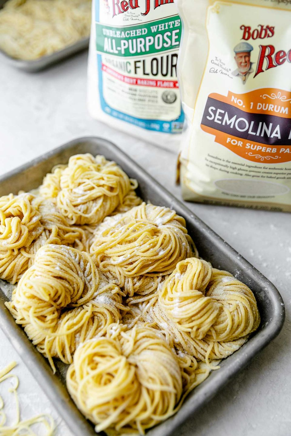 A side angle shot of six bundles of fresh pasta cut into spaghetti noodles are arranged on a small aluminum baking sheet and dusted with semolina flour. The baking sheet sits atop a white textured surface. A few stray noodles, one bag of Bob's Red Mill Organic Unbleached White All-Purpose flour, Bob's Red Mill Semolina flour, & another aluminum baking sheet filled with fresh pasta noodles surround the baking sheet.