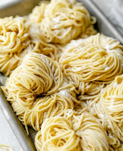 A side angle shot of six bundles of fresh pasta cut into spaghetti noodles are arranged on a small aluminum baking sheet and dusted with semolina flour. The baking sheet sits atop a white textured surface. A light blue napkin & a few stray noodles surround the baking sheet.
