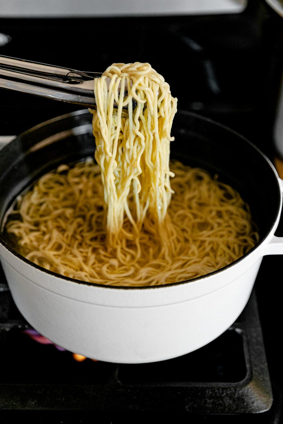 Tongs are used to pick up a bundle of fresh homemade pasta and hold it up over a white pot filled with boiling water and more fresh pasta as it cooks. The pot rests atop a gas stovetop range.