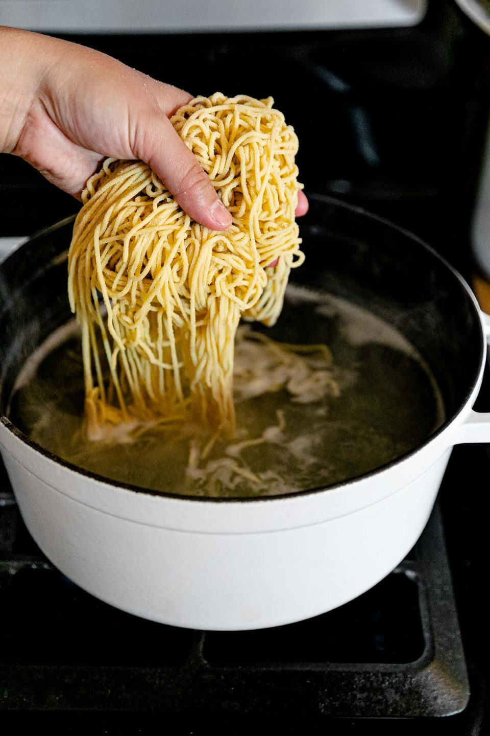 A woman's hand adds fresh homemade pasta to a white pot filled with boiling water. The pot rests atop a gas stovetop range.