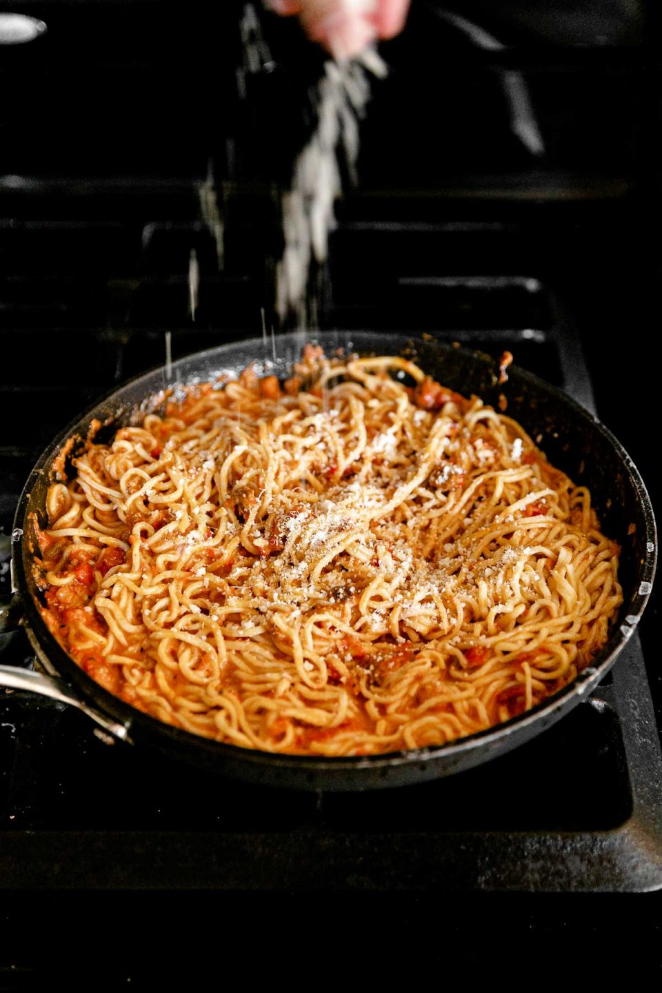A black frying pan filled with fresh homemade pasta tossed in bolognese sauce is dusted with freshly grated parmigiano reggiano. The frying pan rests atop a gas stovetop range.